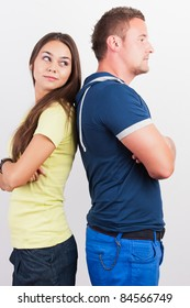 Portrait of a smiling young couple standing back to back on white background