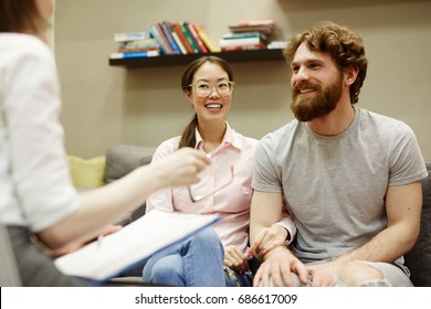 Portrait of smiling young couple visiting advisor for family consultation