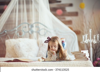 Portrait of a smiling young cute kid reading a book   the bed in a bright big white room