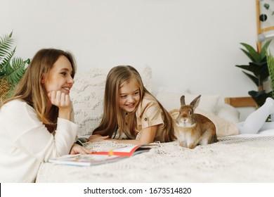 Porträt einer lächelnden jungen, süßen Mutter und Tochter, die ein Buch lesen, entspannen Sie im Bett in einem hellen großen weißen Raum