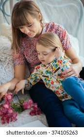 Portrait of a smiling young cute mother and daughter playing with flowers lying and relax in the bed in a bright big white room