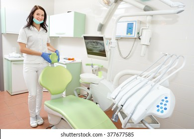 Portrait of a smiling young dentist woman leaning against dentist's chair in dental clinic