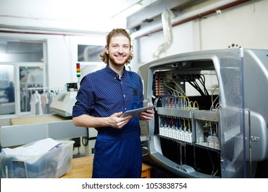 Portrait of smiling young engineer standing near the printing machine