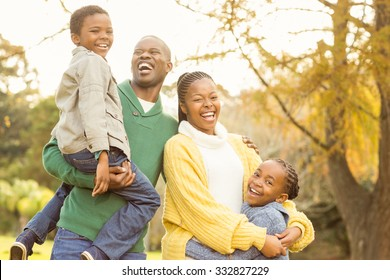 Portrait of a smiling young family laughing on an autumns day
