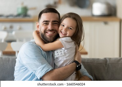 Portrait of smiling young father hug cuddle cute little preschooler daughter look at camera posing at home together, happy dad embrace small girl child show love relax on leisure domestic weekend