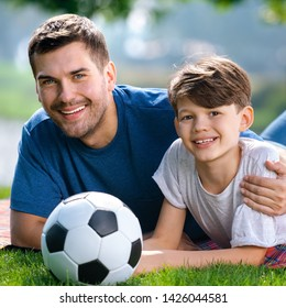 Portrait of smiling young father and son, lying together on a picnic blanket with soccer ball, outdoors. Love, family and happy childhood lifestyle concept. Square composition.