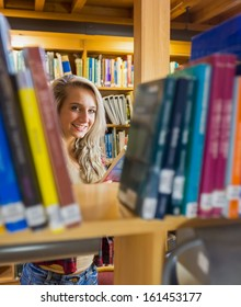 Portrait of a smiling young female amid bookshelves in the college library
