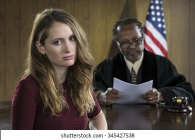 Portrait of a smiling young female attorney with older black male judge in courtroom