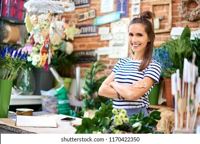 Portrait of smiling young florist standing in front of the counter and looking at camera