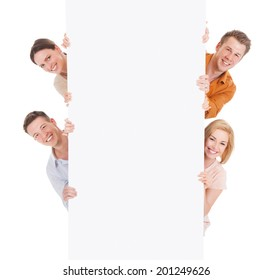 Portrait of smiling young friends looking from behind the blank billboard over white background