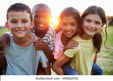 Portrait of smiling young friends piggybacking outdoors