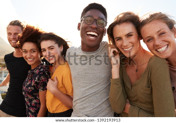 Portrait Of Smiling Young Friends Walking Outdoors Together