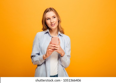 Portrait of a smiling young girl with braces holding mobile phone and looking away at copy space isolated over yellow background