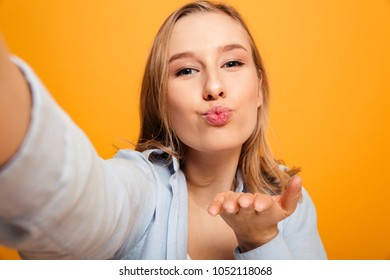 Portrait of a smiling young girl with braces taking a selfie and blowing air kiss isolated over yellow background