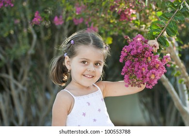 Portrait of smiling young girl with a flower in hand