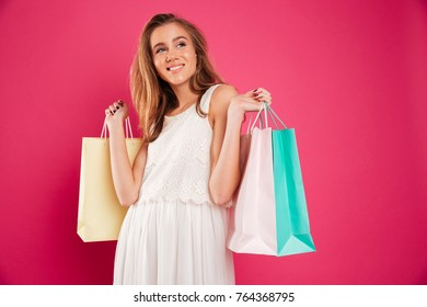 Portrait of a smiling young girl holding shopping bags and looking away at copy space isolated over pink background
