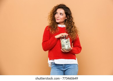 Portrait of a smiling young girl holding jar full of money banknotes and looking away isolated over beige background