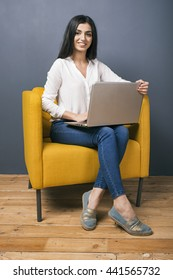Portrait of smiling young girl with laptop on yellow arm-chair looking at camera.