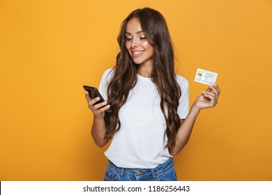 Portrait of a smiling young girl with long brunette hair standing over yellow background, holding mobile phone, showing plastic credit card