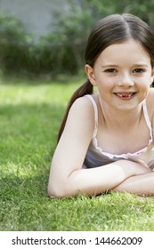 Portrait of smiling young girl lying in grass