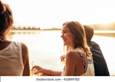 Portrait of smiling young girl sitting by a lake with her friends. Young people enjoying a day at the lake.