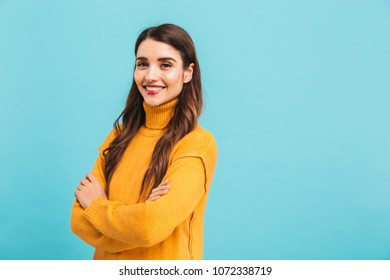Portrait of a smiling young girl in sweater with arms folded looking at camera isolated over blue background