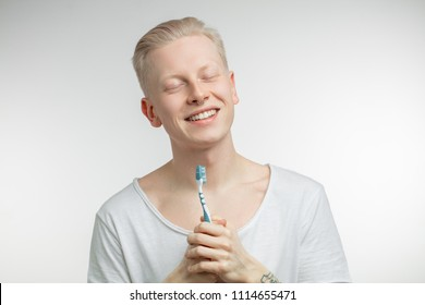 Portrait of smiling young handsome blonde man, floating in clouds with closed eyes, not yet awaken, while keeping toothbrush in tattooed hand. Dental care and teeth health