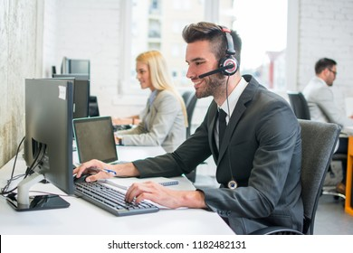 Portrait of a smiling young handsome man in formalwear with headset using computer in a office