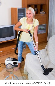 Portrait of smiling young housewife vacuuming in living room