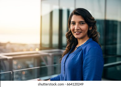 Portrait of a smiling young Indian businesswoman standing outside on an office building balcony overlooking the city at dusk