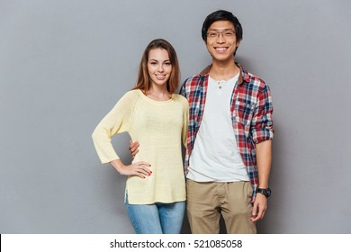 Portrait of a smiling young interracial couple hugging and looking at camera isolated on the gray background