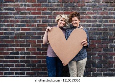Portrait of a smiling young lesbian couple holding a heart symbol while standing outside together in front of a brick wall