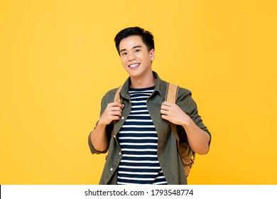 Porträt eines lächelnden jungen männlichen asiatischen Touristen mit einem Rucksack, der auf isoliertem, gelbem Hintergrund bereithält