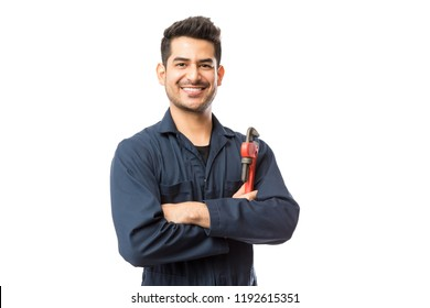 Portrait of smiling young male plumber with pipe wrench standing arms crossed on white background