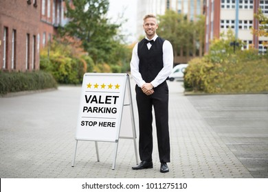 Portrait Of A Smiling Young Male Valet Standing Near Valet Parking Sign