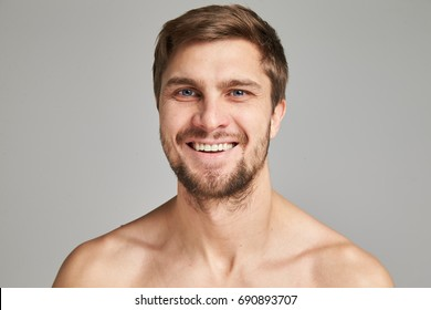 Portrait of a smiling young man with bare swimmers shoulders on a gray background, powerful, beard, charismatic, adult, brutal, athletic, edited photo, bright smile, white teeth smile, look in camera