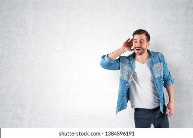 Portrait of smiling young man in casual clothes listening attentively with his palm near ear standing near concrete wall. Concept of curiosity and eavesdropping. Mock up