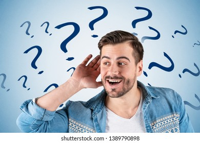 Portrait of smiling young man in casual clothes listening attentively with his palm near ear standing near blue wall with question marks drawn on it. Concept of curiosity and eavesdropping
