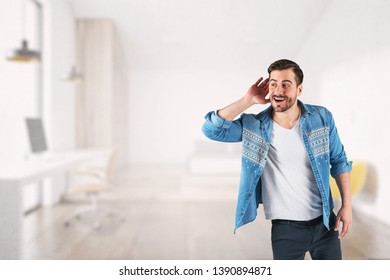 Portrait of smiling young man in casual clothes listening attentively with his palm near ear standing over blurred office background. Concept of curiosity and eavesdropping. Mock up