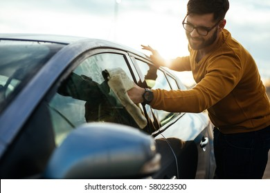 Portrait of a smiling young man cleaning his car with a microfiber cloth outdoors.