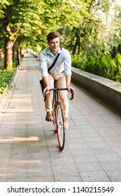 Portrait of a smiling young man dressed in shirt with bag riding on a bicycle outdoors