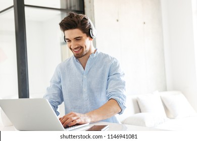 Portrait of a smiling young man in earphones using laptop computer while sitting at home