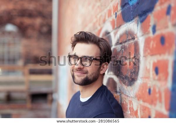眼鏡をかけ、レンガ壁に寄りかかった顔の毛を持つ微笑む青年のポートレート