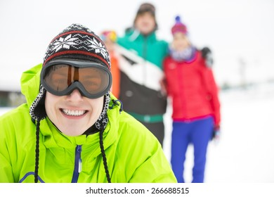Portrait of smiling young man with friends in background during winter