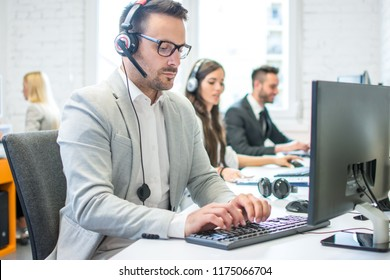 Portrait of a smiling young man with headset using computer in the office