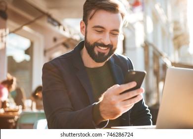 Portrait of a smiling young man holding mobile phone while sitting at the cafe outdoors