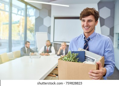 Portrait of smiling young man holding box of personal belongings being hired to work in business company, copy space