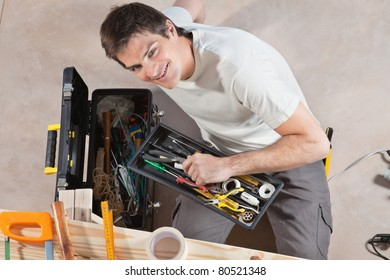 Portrait of smiling young man holding his tool box