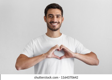 Portrait of smiling young man keeps hands on chest in heart shape sign, expresses sympathy. Kind hearted friendly nice guy wearing blank white t-shirt