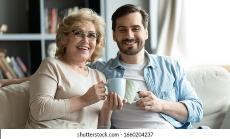 Portrait of smiling young man and middle-aged mother sit relax on couch in living room drinking tea or coffee together, happy mature mom and grown-up adult son rest at home enjoying family weekend